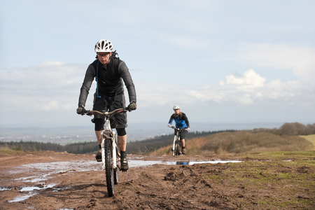 dirtied: Couple mountain biking in countryside