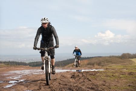 pursued: Couple mountain biking in countryside