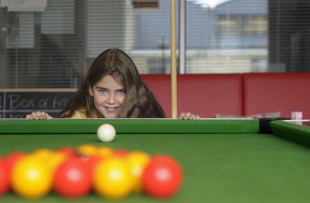 resolving: Young girl playing pool