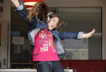 musically: Girl wearing headphones jumping