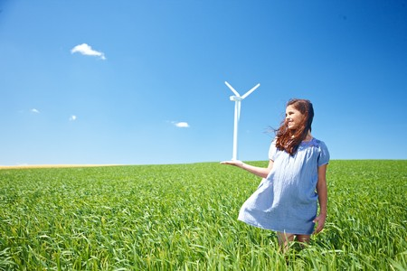 Girl on field with wind turbine