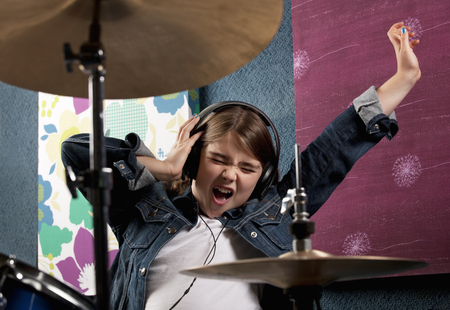 musically: Girl listening to headphone with drums