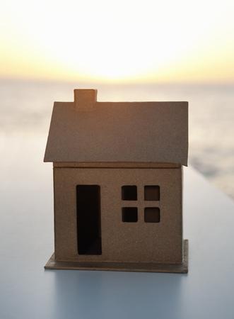 A cardboard house shot against the sea