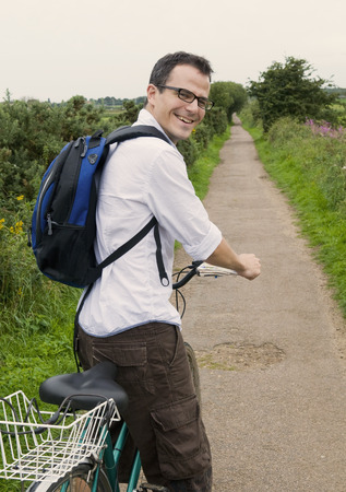 Happy man prepares to bicycle in country