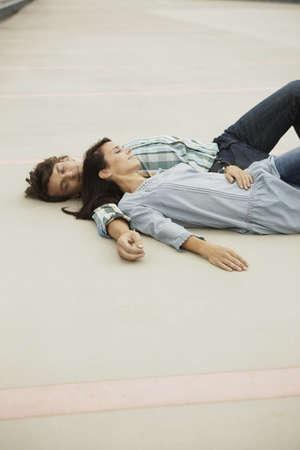 cuddled: Couple sleeping on park deck