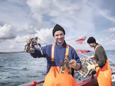 Fishermen on boat holding lobsters LANG_EVOIMAGES