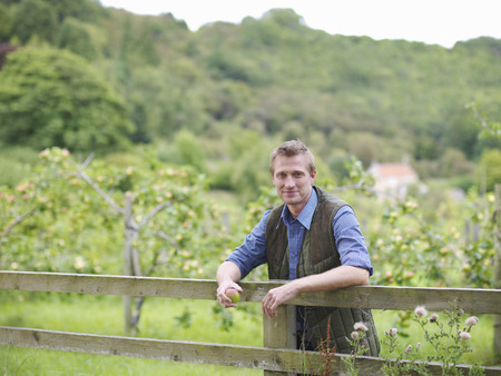 leaning by barrier: Farmer leans on fence outside orchard LANG_EVOIMAGES