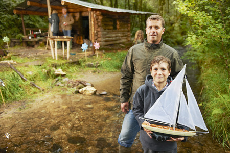 poppa: Father and son holding sailing boat