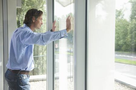 musing: Man looking through office window LANG_EVOIMAGES