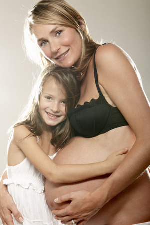 Pregnant woman with daughter,smiling LANG_EVOIMAGES