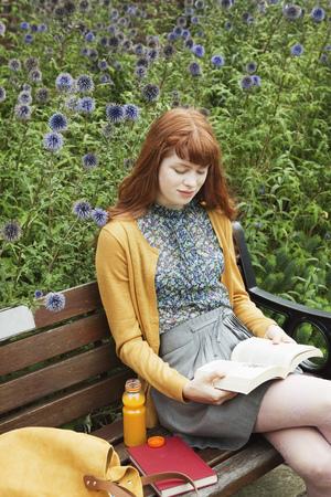 refreshed: Woman reading on bench LANG_EVOIMAGES