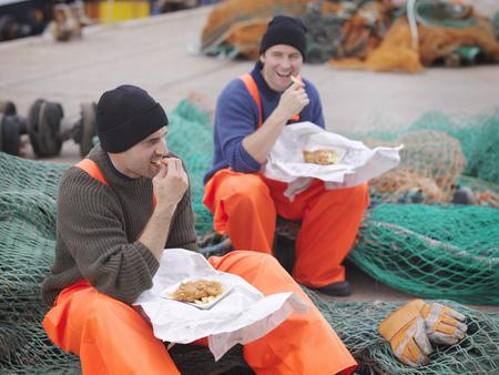 Fishermen eating fish and chips LANG_EVOIMAGES