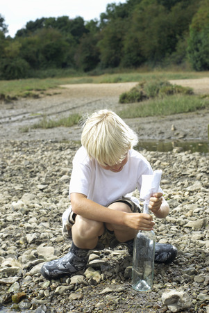 Boy pulling message from bottle
