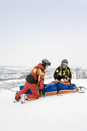 gurney: Two Rescuers helping skier LANG_EVOIMAGES