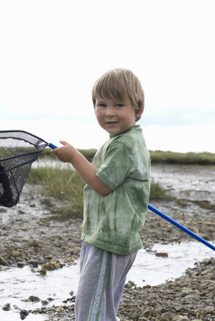 omnivore: Young boy holding fishing net up