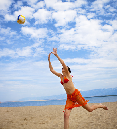 a rehearsal: Woman playing volleyball at the beach LANG_EVOIMAGES