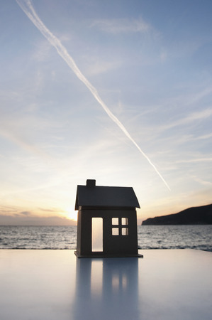 aspirational: A cardboard house set against a sunset