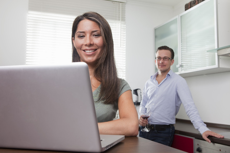 telecommuter: Woman and man using laptop at home