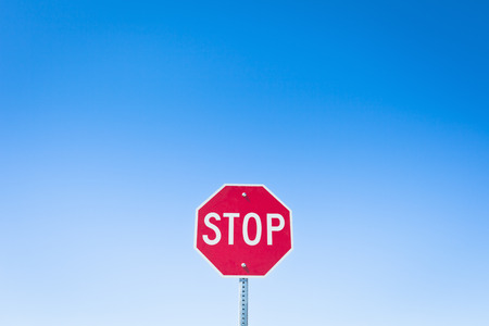 cautions: Stop sign against blue sky