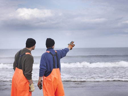 Fishermen on shore pointing out to sea LANG_EVOIMAGES