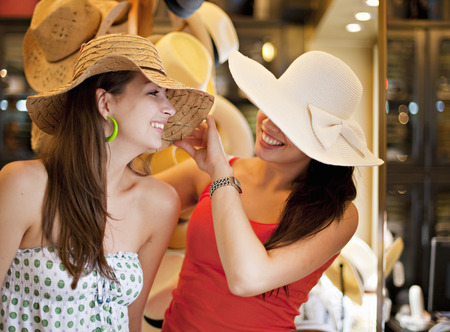 indecisive: Young women trying on hats