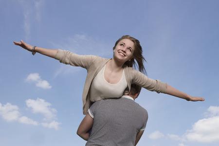 Girl flying on boys shoulders