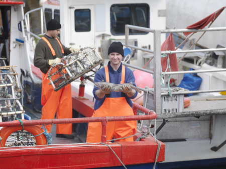 Fisherman holds fish on boat in harbour