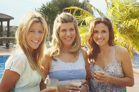 Portrait of three smiling women by pool LANG_EVOIMAGES