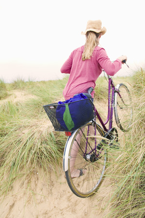 Women pushes bicycle over beach LANG_EVOIMAGES