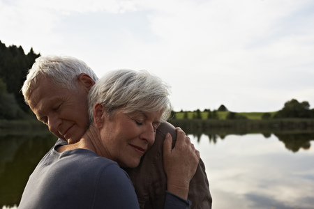grays: Senior couple hugging in front of lake