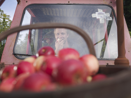 assembled: Farmer in tractor eating apple