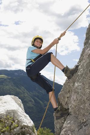 rockclimber: Boy climbing a rock with a rope