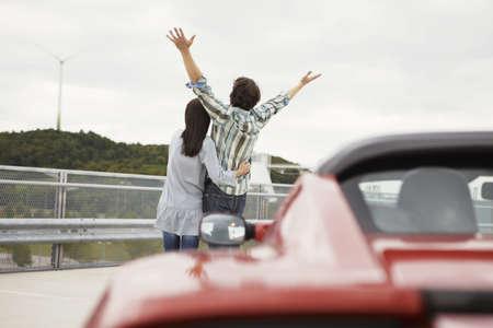 alternative living: Couple close together near electric car