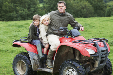 transportation: Father and kids on quad bike