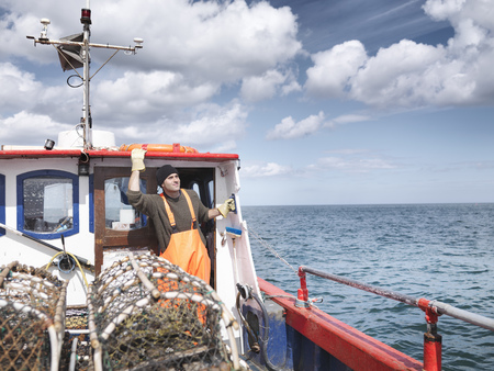 defended: Fisherman looks out to sea on boat LANG_EVOIMAGES