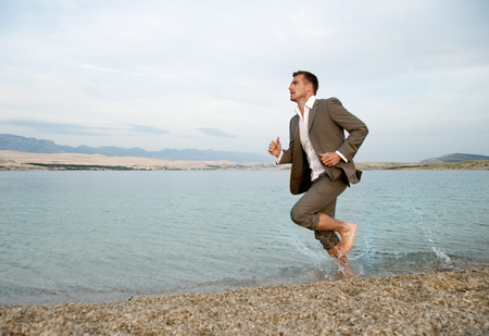 out of context: Businessman running on the beach
