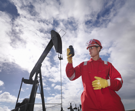Worker inspecting crude oil at oil well