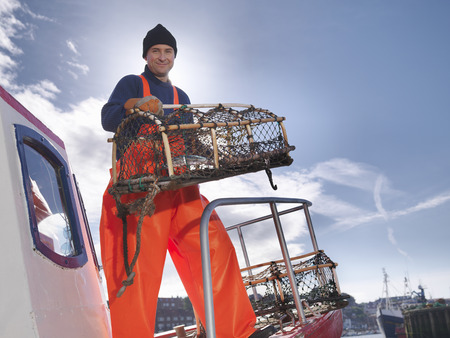 Fisherman with lobster pot on boat