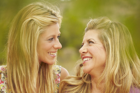 equivalents: Mother & daughter smiling at each other LANG_EVOIMAGES