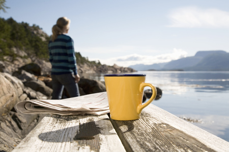 Coffee and paper,woman in background