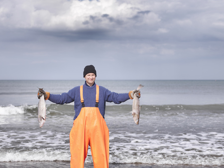 Fisherman on shore holding fish LANG_EVOIMAGES
