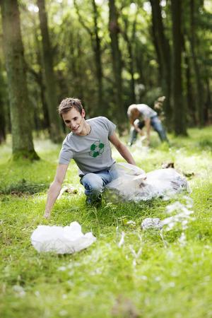 agachado: Joven recogiendo basura en la naturaleza