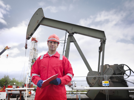 well beings: Worker in front of oil well pump