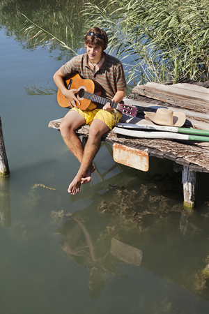 Man sitting on jetty playing a guitar