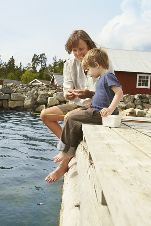 midsummer pole: Woman with grandson fishing from jetty LANG_EVOIMAGES