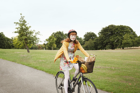 Young woman cycling through park