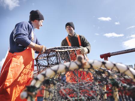 Fishermen loading boat with lobster pots LANG_EVOIMAGES