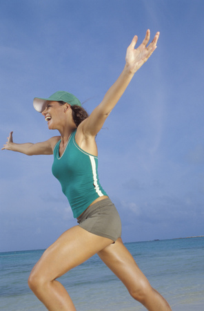 exhilarating: Woman running on beach LANG_EVOIMAGES