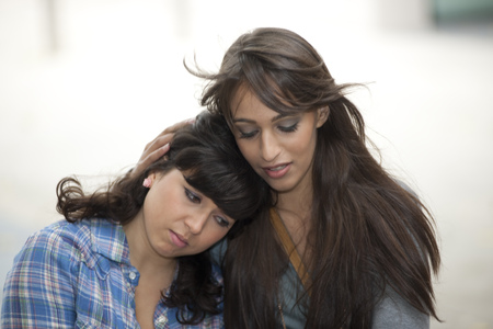 in twos: Young female consoling friend