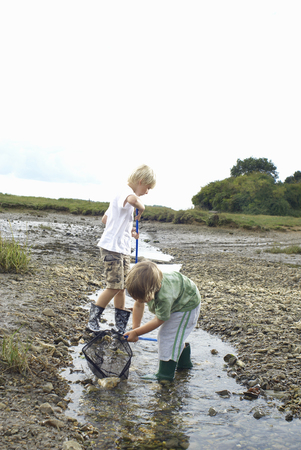 Two boys fishing with nets in a stream